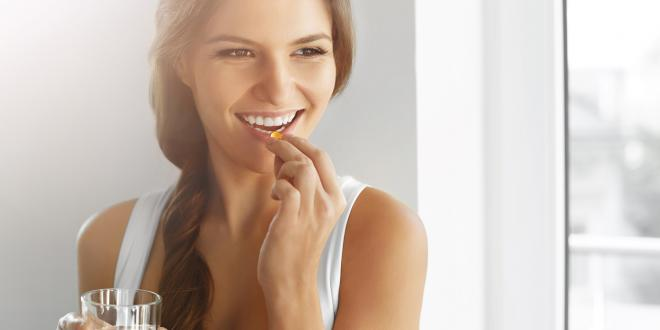 Close up of happy a healthy, smiling woman taking a vitamin or supplement.